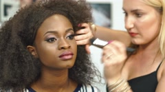 Woman makeup artist applying and correcting sparkling makeup on fabulous black - stock footage