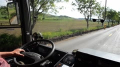 Bus moving on a road with two lanes bordered by trees Stock Footage