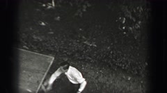 1937: Outdoor table tennis game aerial pov man playing in formal dress clothes. Stock Footage