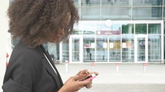 Side view of attractive black business lady texting on phone while waiting for a Stock Footage