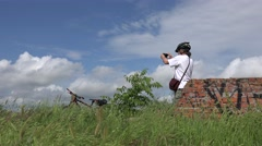 Cyclist photographed on mobile phone, against background of fantastic sky - stock footage