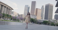 Attractive young Asian woman wearing a gold sequined dress poses in front of  Do Stock Footage