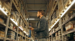 Manager With Tablet PC Checking Goods At Supermarket Warehouse Stock Footage