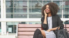 Fabulous smiling african american business woman sitting on the bench at the - stock footage