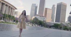 Beautiful Asian woman in gold dress stretches arms in front of LA skyline 4K Stock Footage