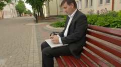 Businessman tweeting on cellphone sitting on a bench in the street - stock footage