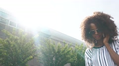 Attractive black african american woman in sunglasses talking on the phone. Sky Stock Footage