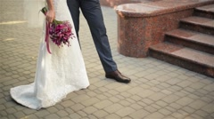 feet of bride and groom walking, wedding shoes, bridal bouquet - stock footage