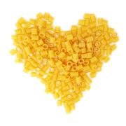 Heart shape made of dry ditalini pasta over isolated white background - stock photo