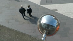 People walking high angle under metal orb ball - Stockholm in Summer sunshine Stock Footage