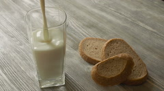 Pouring glass of milk and grain bread on background wooden table Stock Footage