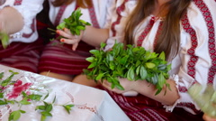 Female hands with bracelets making wreath from wild field plants Stock Footage