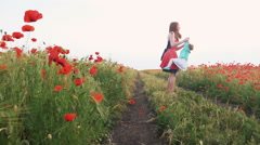 Mother whirling with her child in poppy field, slow motion - stock footage