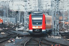 Railway station with modern red commuter train at sunset - stock photo