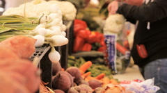 Shoppers buying fresh vegetables and fruits at the farmers market in the summer - stock footage