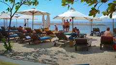 Tourists relaxing on a private resort's beach in Sanur, Bali, Indonesia Stock Footage