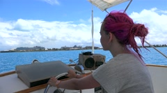 Girl with pink hair drives a speedboat at Atlantic Ocean. Bermuda Stock Footage