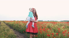 Mother walking with her baby daughter in poppy field - stock footage