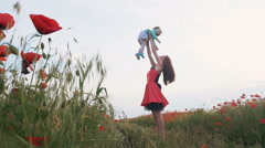Mother throwing up her baby daughter in poppy field, slow motion - stock footage