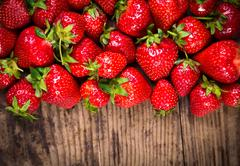 food background with strawberry on wood table - stock photo