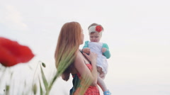 Mother with her baby daughter in poppy field - stock footage