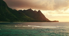 Aerial view flying over ocean reef and waves into dramatic sunset on Kauai Stock Footage