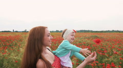 Mother playing with her child in poppy field, slow motion - stock footage