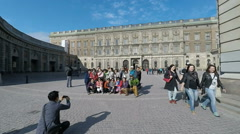 Chinese tourists pose for photo outside Royal palace, Stockholm Stock Footage