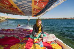Tourist eating snack during felucca trip on the Nile. - stock photo