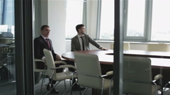 Secretary woman in a red jacket brings coffee for a boss. Two businessmen. Stock Footage