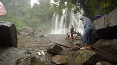 Tourists pose for pictures at base of a waterfall at Phnom Kulen National Par - stock footage