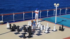 Young boy plays chess with his grandfather on the desk of the cruise ship Stock Footage