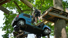 A car is hanging from the trees and a man is passing through the car Stock Footage