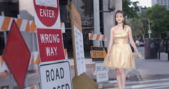 Asian woman in gold dress with road work signs Downtown LA 4K Stock Footage