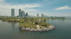Establishing aerial shot of city from over water. 4K filmic footage. - stock footage