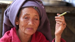 Old woman smoking a big handmade cigar. Inle lake, Myanmar, Burma. Close up - stock footage