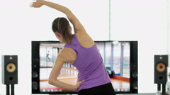 Woman doing fitness at home with dumbbells using on screen TV instructions HD - stock footage
