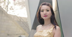 Attractive Asian woman in cocktail dress waiting by steel wall 4K - stock footage