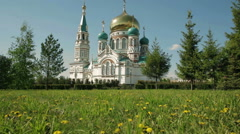 Uspensky Cathedral in Omsk on background of green lawn with yellow dandelions Stock Footage