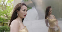 Beautiful Asian woman in cocktail dress standing by steel wall 4K - stock footage