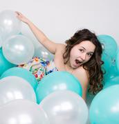 beautiful curly girl in a multi-colored dress playing with balloons - stock photo