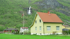 House in Norwegian village with waterfall background Stock Footage