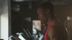 Side view of muscular handsome black man jogging on a treadmill in the gym - stock footage