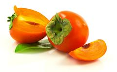 Group of ripe fresh persimmons with slices and leaves - stock photo