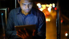 Handsome, young asain man with tablet computer in city at night Stock Footage