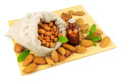 Almonds in the sack and almond oil Stock Photos