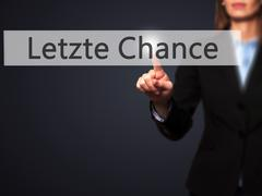 Letzte Chance (Last Chance in German) - Businesswoman hand pressing button on Stock Photos