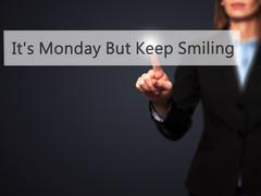 It's Monday But Keep Smiling  - Businesswoman hand pressing button on touch s Stock Photos