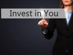 Invest in You - Businesswoman hand pressing button on touch screen interface. Stock Photos