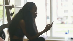 Beautiful black woman with luxury long hair texting on her smartphone indoor - stock footage